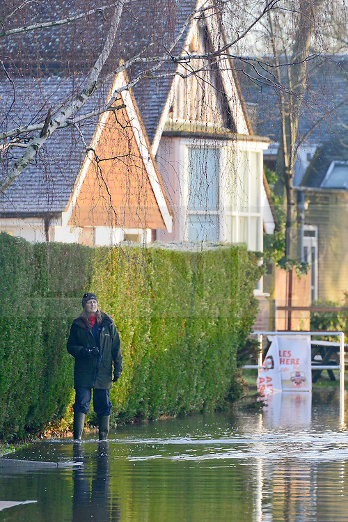 © Licensed to London News Pictures. 12/01/2014. Wraysbury, UK. People watch the floodwater. Flooding in Wraysbury, Berkshire today 12th January 2014.  Flooding and property damage is expected to continue along the River Thames.  Large areas of Britain are experiencing flooding after wet weather. Photo credit : Stephen Simpson/LNP