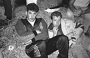 Two ravers sat on hay bales at party, UK, 1980s.