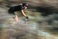 Late 20's Caucasian man riding Mountain bike on a trail through Sage brush.  Blur, panning shot.<br />