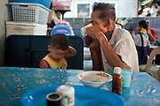 Sept. 23, 2009 -- BANGKOK, THAILAND: A man and his son finish their breakfast in a small shop in the Khlong Toey slum area in Bangkok. Khlong Toey slum in Bangkok, Thailand, is the largest slum area in Bangkok. Photo by Jack Kurtz