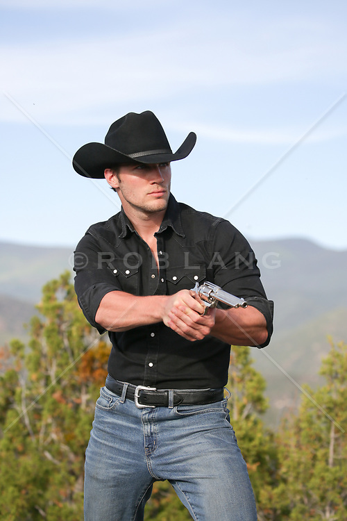 cowboy with a gun out on a ranch