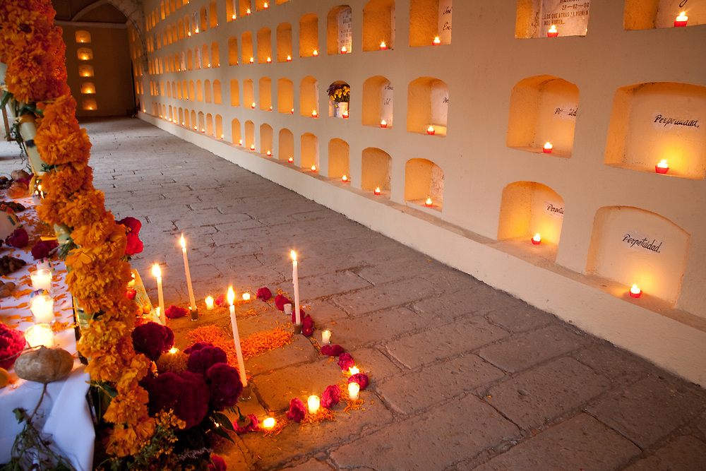 North America, Mexico, Oaxaca Province, Oaxaca, Pantheon San Miguel Cemetery, altar in hall with rows of tombs, some dating back to the 1800s, lit with candles for annual Day of the Dead (Dias de los Muertos) celebration in November