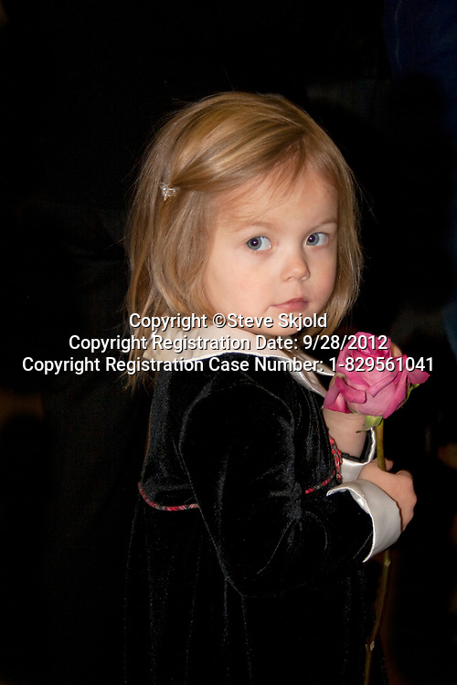 Girl age 3 carrying red rose at family funeral. Monticello Minnesota MN USA