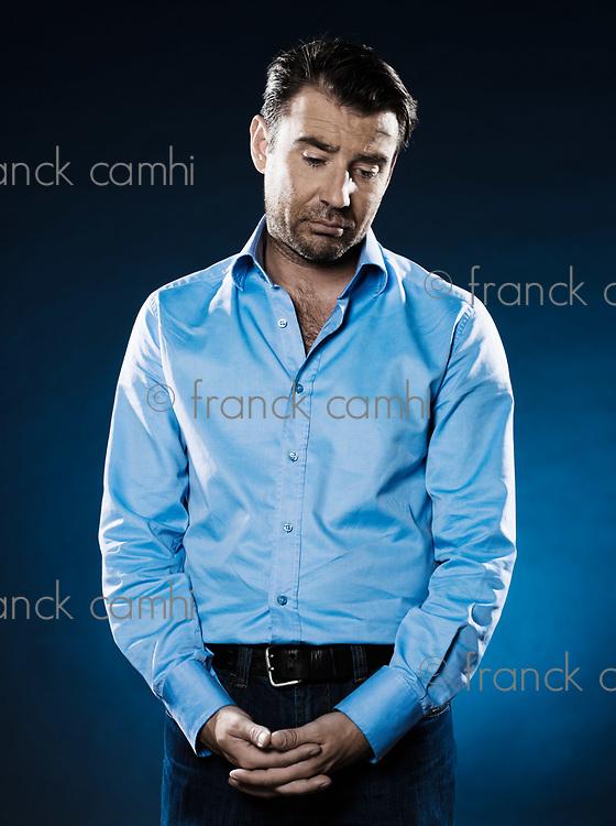 caucasian man unshaven frown sulk portrait isolated studio on black background