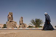 A local Egyptian man walks past the ancient Egyptian Colossi of Memnon site, Luxor, Nile Valley, Egypt. The Colossi of Memnon (memorial temple of Amenophis III) are two massive stone statues of Pharaoh Amenhotep III, who reigned during Dynasty XVIII. For the past 3,400 years (since 1350 BC) they have stood in the Theban necropolis, west of the River Nile from the modern city of Luxor.