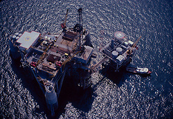 Stock photo of an offshore drilling rig next to a production platform in Gulf of Mexico.
