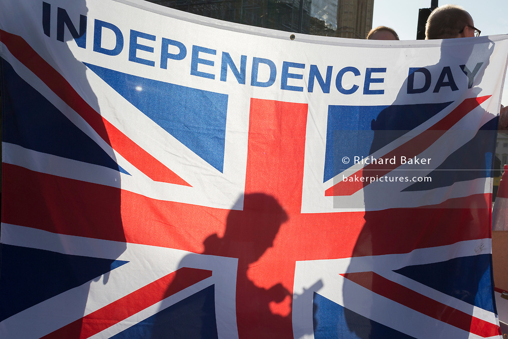 On the day that Members of Parliament sat on a Saturday (the first time in 37 years and dubbed 'Super Saturday') in order to vote for Prime Minister Boris Johnson's Brexit deal with the EU in Brussels, Brexiters stand against a Union Jack while a million Remainers (according to organisers) marched through the capital to voice their opposition to a Brexit and calling for a peoples' Vote, on 19th October 2019, in London, England.