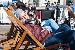 © Licensed to London News Pictures. 30/03/2016. Brighton, UK. A young woman relaxes on Brighton Pier as the weather has turned mild and sunny. Photo credit: Hugo Michiels/LNP