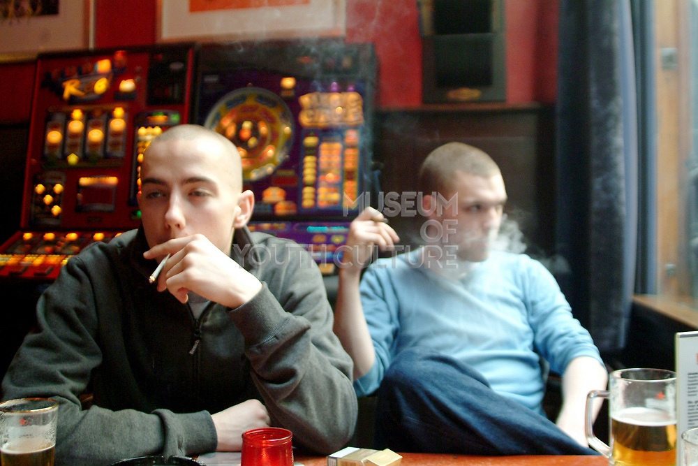 Two friends sitting in a coffee shop drinking beer and smoking spliffs, Amsterdam, Netherlands, 2000's