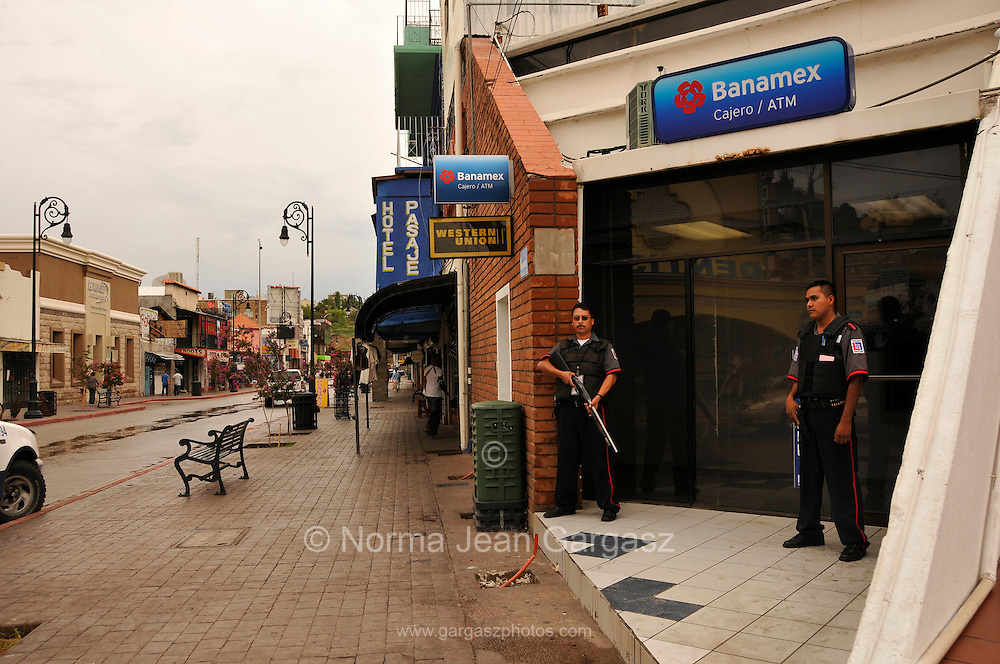 Armed security guards stand watch at a bank entry along Calle Obregon in Nogales, Sonora, Mexico, across the border from Nogales, Arizona, USA.  Streets are mostly void of patrons as businesses in Nogales, Sonora, experience an economic decline as reports of cartel violence deter tourists and shoppers from entering the country.