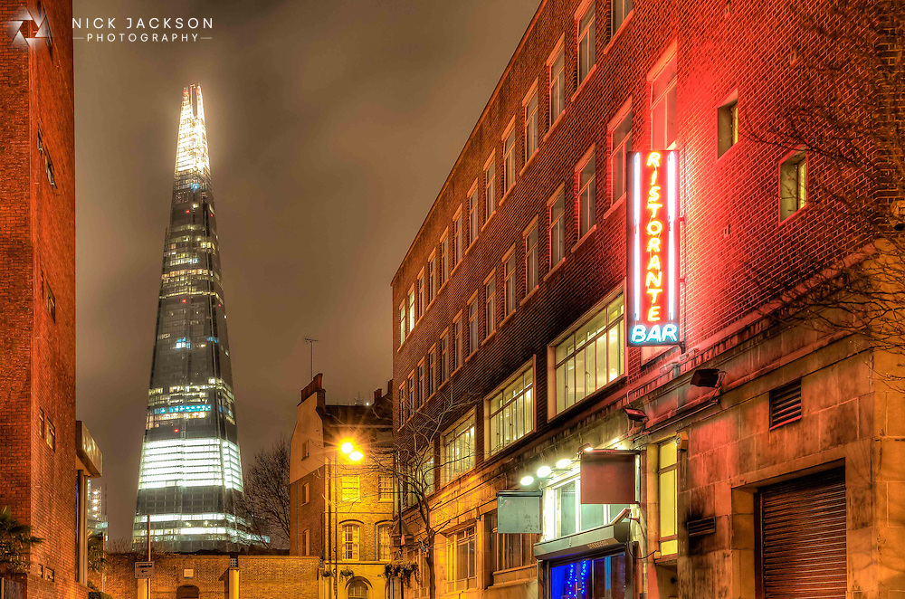 The 87-storey skyscraper, known as The Shard, towers over the neon foreground of a Southwark backstreet