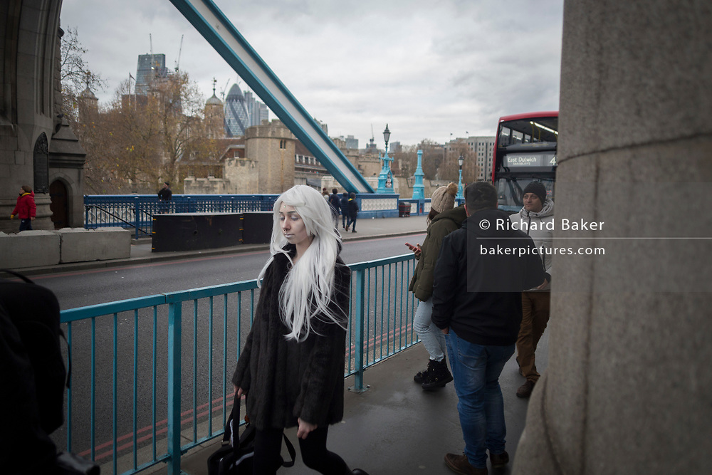A woman in pale make-up and white hair crosses Tower Bridge, on 6th December 2017, in London England.