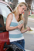 Young woman counting money at service station