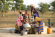Women get water from a hand pump outside their village.