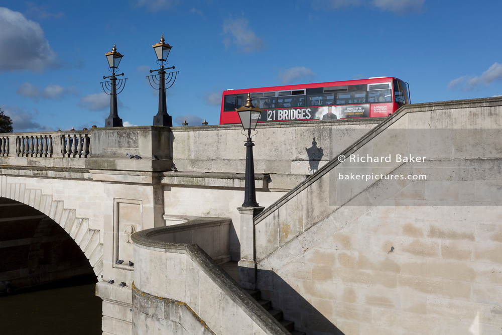 Seen from the southern bank of the river Thames is the architecture of Kingston Bridge where a London bus is driving over with an ad on the side for the film '21 Bridges', on 7th November 2019, in Kingston, London, England. A crossing has existed at Kingston since ancient times and this version of Kingston Bridge was constructed by Herbert for £26,800 and opened by the Duchess of Clarence (the future Queen Adelaide) on 17 July 1828. Constructed from Portland stone, it comprises of five elliptical arches.