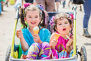 Sisters enjoy an icecream while being towed around in a cart by their parents. The 2015 Glastonbury Festival, Worthy Farm, Glastonbury.