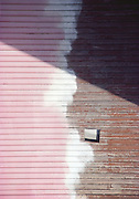 a wall of half painted wooden siding is bisected by a shadow.