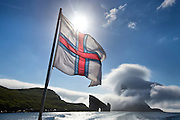The Faroese flag flies on the stern of the passenger ferry from Mykines to Sørvágur.  Drangonir, a sea stack with a natural arch stands off the coast of the island of Vagar. The island of Tindholmur is in the background covered by clouds.