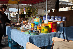 A typical antiques/collectibles booth offers old cannisters and food boxes for sale at the sunday flea market in L'Isle-sur-la-Sorge.  Vintage clothing, toys, and antiques share sidewalk space with amazing food and working artists during these Sunday flea for which the town is famous.