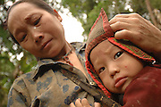 "Ms. Mee Moua Vang, with her baby, Li Cheng Vang, near Vang Vieng, Laos, July 4, 2006.  Her message  to the world, ""My husband and two older daughters were killed by the communist while foraging for food.  My daughter Blee was attacked by the communist where her guts were sticking out and I was unable to help her so she died.  I miss her very much.  I am desperately suffering here with no help.  I ask you to come in and save us.  Bring us food.""..**EXCLUSIVE, no tabloids without permission**"