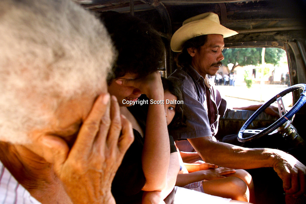 Family members cry as they flee Chengue by car the day after a massive paramilitary massacre. Millions of Colombians are internally displaced from the violence of the civil war. (Photo/Scott Dalton)