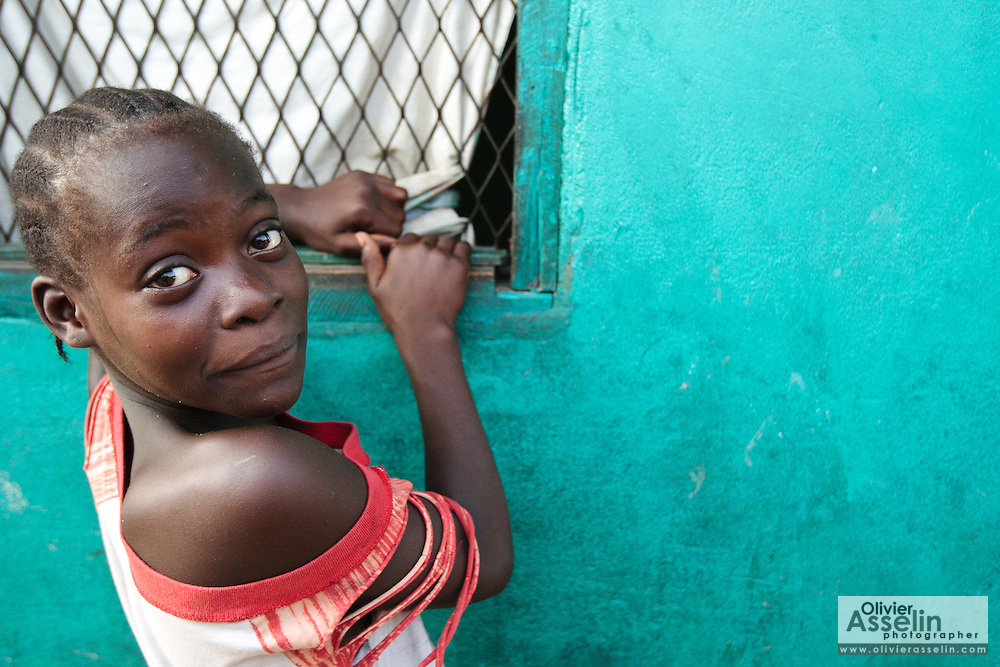 A girl looks back while watching TV through a window in the West Point slum of Monrovia, Montserrado county, Liberia on Monday April 2, 2012.