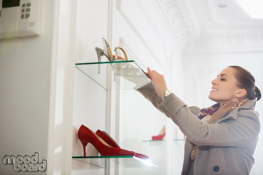 Young woman admiring footwear in store