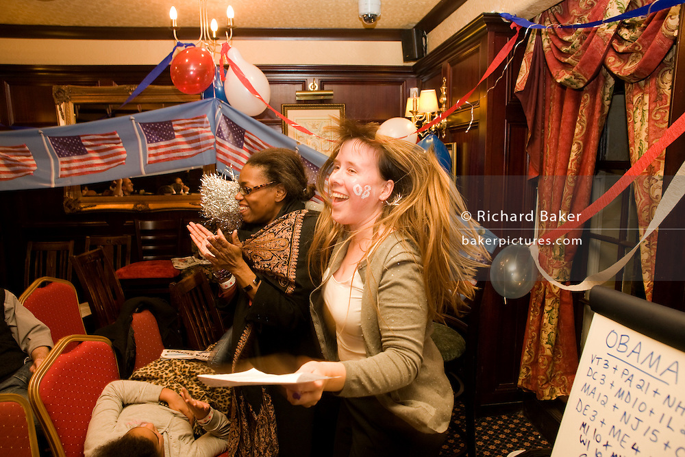 Democrat members celebrate as Barack Obama is declared winner of another US state during overnight election party in London