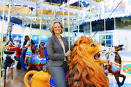 Garden City, New York, USA. March 9, 2019.  LAURA CURRAN, the Nassau County Executive, (wearing gray suit) rides Nunley's Carousel during Unveiling ceremony of mural by painter Michael White, of close-up of a Nunley's Carousel horse. Event was held at historic Nunley's Carousel in its Pavilion on Museum Row on Long Island. After speeches by elected officials and members of Baldwin Civic Association and Baldwin Historical Society, and others, people enjoy free carousel rides and food.