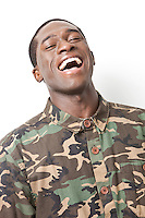 Portrait of cheerful young military soldier in camouflage clothing laughing against white background