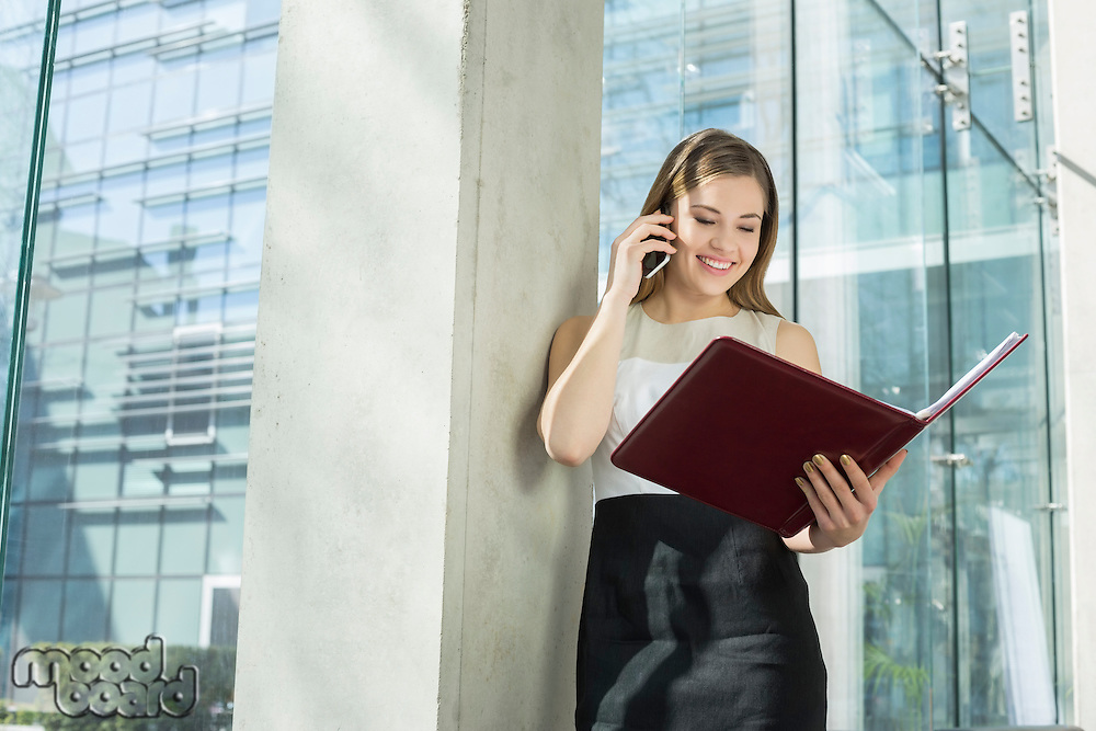 Happy businesswoman using cell phone while reading file in office