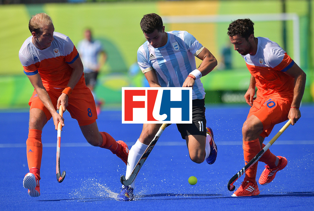 Argentina's Joaquin Menini (C) fights for the ball with the Netherland's Billy Bakker (L) and  Valentin Verga during the men's field hockey Argentina vs Netherlands match of the Rio 2016 Olympics Games at the Olympic Hockey Centre in Rio de Janeiro on August, 6 2016. / AFP / Carl DE SOUZA        (Photo credit should read CARL DE SOUZA/AFP/Getty Images)
