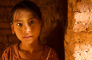 A young girl whose father sells traditional paintings poses for a portrait before beginning her sales pitch at an ancient pagoda in Bagan (Pagan), Myanmar (Burma).