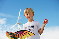 Boy (7-9) holding kite at wind farm, portrait