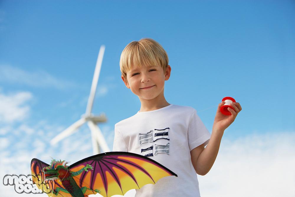 Boy (7-9) holding kite at wind farm, portrait