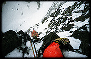 Steve Cooke seconds a steep pitch in a snow blizzard, just below the summit of Batian 5199m (17,057ft), South-West Ridge Route (Grade IV), Mount Kenya. Crevasses on the Tyndall Glacier beckon 600m below.