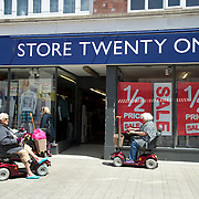 Bognor Regis, Sussex. Two people on  mobility scooters outside a shop advertising a half-price sale.