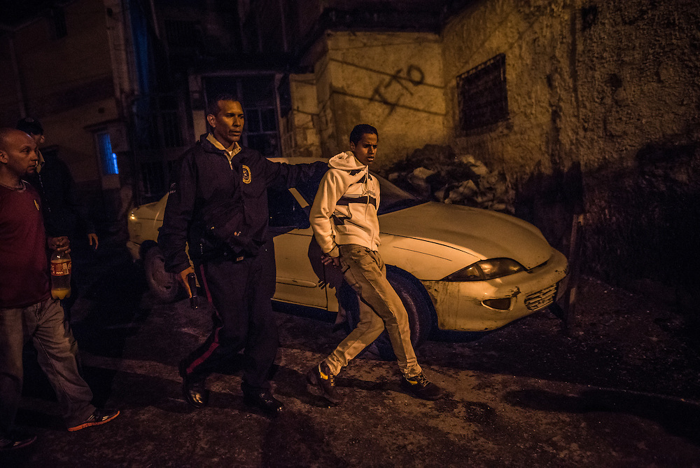 CARRIZAL, VENEZUELA - DECEMBER 10, 2016:  Police officers detain a man who they suspected was carrying some sort of contraband  on his person, because he ran from them while they were patroling a slum in Carrizal, Venezuela. A severe economic crisis in Venezuela, caused by the drop in oil prices and years of economic mismanagement under a Socialist government, has lead to an alarming rise in crime and insecurity in the country.  Hyperinflation has left both the working class and professional class of workers with salaries that cannot purchase enough food to feed their families. Many people are turning to crime to make ends meet.  PHOTO: Meridith Kohut for The New York Times