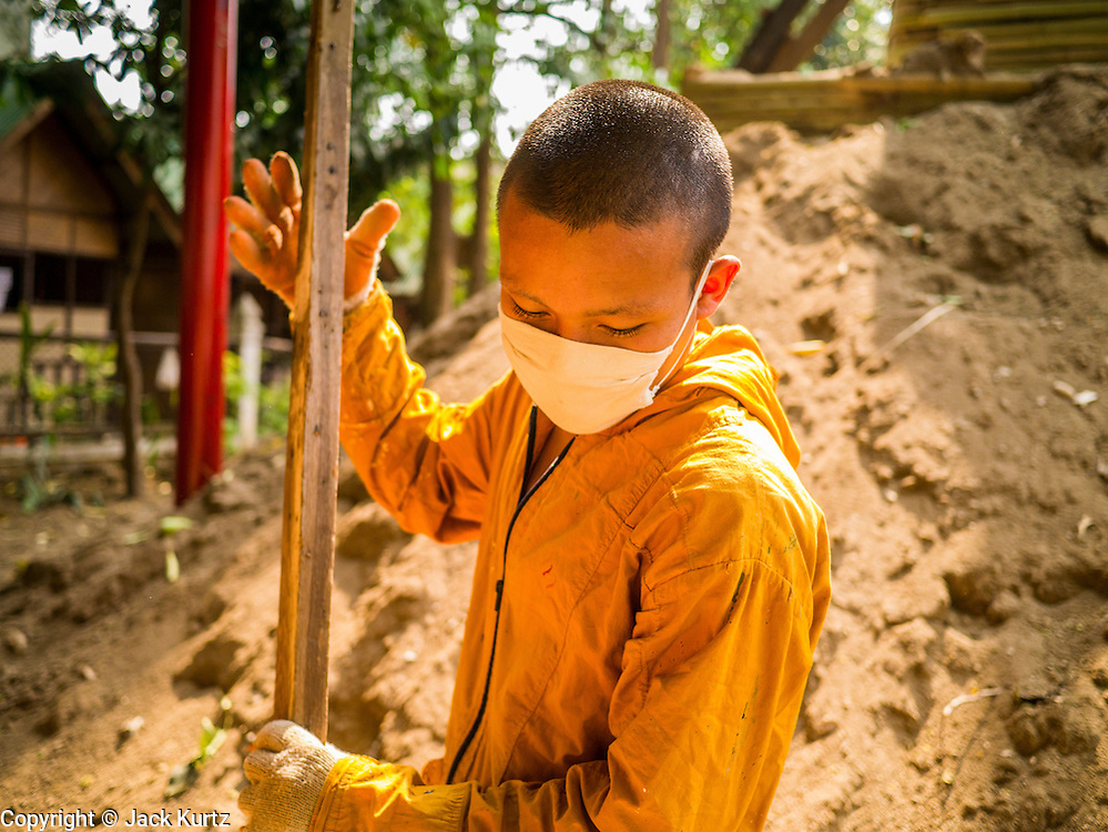 "07 APRIL 2013 - CHIANG MAI, CHIANG MAI, THAILAND: A Buddhist novice wearing a mask to block out smoke and pollutants works with his fellow novices at Wat Jetlin in Chiang Mai. The ""burning season,"" which roughly goes from late February to late April, is when farmers in northern Thailand burn the dead grass and last year's stubble out of their fields. The burning creates clouds of smoke that causes breathing problems, reduces visibility and contributes to global warming. The Thai government has banned the burning and is making an effort to control it, but the farmers think it replenishes their soil (they use the ash as fertilizer) and it's cheaper than ploughing the weeds under.   PHOTO BY JACK KURTZ"