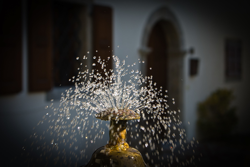 Old water fountain in front of traditional house in Carnia, Italy