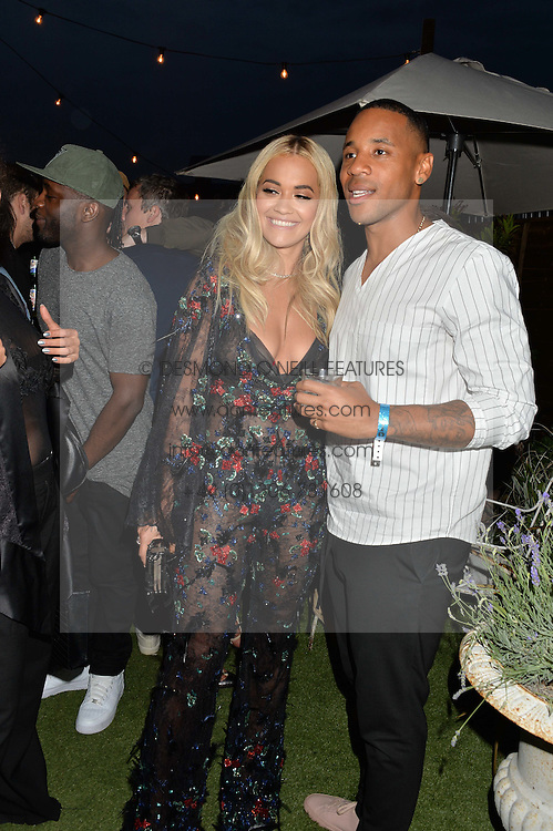 RITA ORA and REGGIE YATES at the Warner Music Group & GQ Summer Drinks hosted in asociation with Quintessentially at Shoreditch House, Ebor Street, London on 6th July 2016.