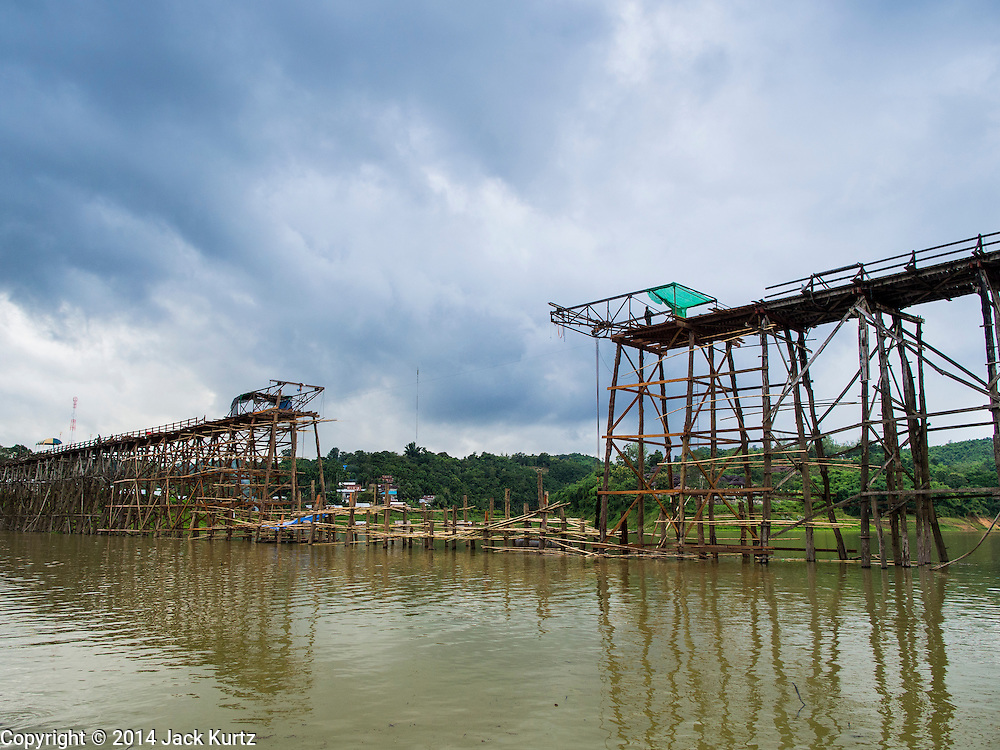 15 SEPTEMBER 2014 - SANGKHLA BURI, KANCHANABURI, THAILAND:  The 2800 foot long (850 meters) Saphan Mon (Mon Bridge) spans the Song Kalia River. It is reportedly second longest wooden bridge in the world. The bridge was severely damaged during heavy rainfall in July 2013 when its 230 foot middle section  (70 meters) collapsed during flooding. Officially known as Uttamanusorn Bridge, the bridge has been used by people in Sangkhla Buri (also known as Sangkhlaburi) for 20 years. The bridge was was conceived by Luang Pho Uttama, the late abbot of of Wat Wang Wiwekaram, and was built by hand by Mon refugees from Myanmar (then Burma). The wooden bridge is one of the leading tourist attractions in Kanchanaburi province. The loss of the bridge has hurt the economy of the Mon community opposite Sangkhla Buri. The repair has taken far longer than expected. Thai Prime Minister General Prayuth Chan-ocha ordered an engineer unit of the Royal Thai Army to help the local Mon population repair the bridge. Local people said they hope the bridge is repaired by the end November, which is when the tourist season starts.   PHOTO BY JACK KURTZ