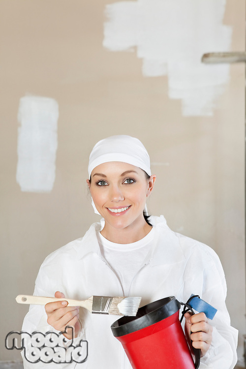 Portrait of a happy female worker holding a paint brush and bucket
