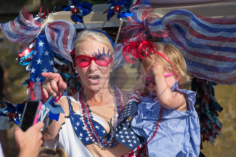 A grandmother holds her young granddaughter during the annual Sullivan's Island Independence Day parade July 4, 2017 in Sullivan's Island, South Carolina. The tiny affluent sea island hosts a bicycle and golf cart parade through the historic village.