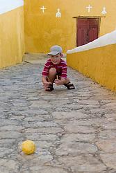 Mexico, Yucatan, Izamal, boy (age 8) playing with ball in Convento de San Antonio de Padua, built 1533-1561.  MR