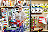 Portrait of a mature man with shopping cart in hardware store