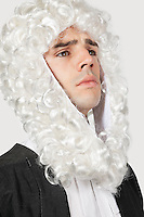 Young man dressed as judge against gray background