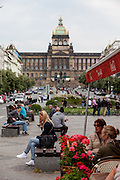 """Prague Wenceslas Square with the National Museum (Narodni Muzeum) and the Statue of St. Wenceslas in the back. One the right side """"Cafe Tram""""."""