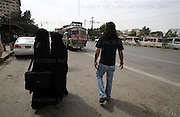 Ibad 27 years old from the middle class family walk on the bust stand, while women wearing the traditional burqa and hijaab waits for bus on Thursday 22, 2007 in Karachi, Pakistan..Pakistan most known as an Islamic Taliban and lake of tolerant, certain youths from the middle class and upper class is finding its way out, one foot in tradition and the other in western way of life.