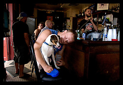 "3rd Sept, 2005. Hurricane Katrina aftermath. New Orleans. Johnny White's Sports Bar on Bourbon Street in the French Quarter - with it's claim to ""Never Close."" The bar has remained open throughout. John Webster gives his dog Muffin a drink at the bar."